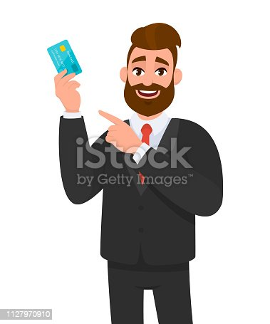 Smiling young business man holding or showing a credit, debit, ATM or banking card and pointing towards with hand and finger. Man wearing black suit and red colour tie. Vector concept illustration.