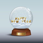 Snow globe with 2018 Happy New Year signs. HAPPY NEW YEAR letters inside snow globe and golden badge with 2018 number on brown wooden base. Vector Christmas and New Year design element.