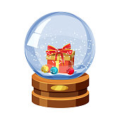 Snow globe with shiny snow and gift box with Christmas ball, golden badge on brown wooden base. Vector Christmas design element. Cartoon style, vector, isolated