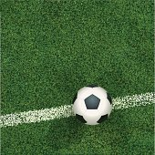 Soccerball seen from above on grass and chalkline.