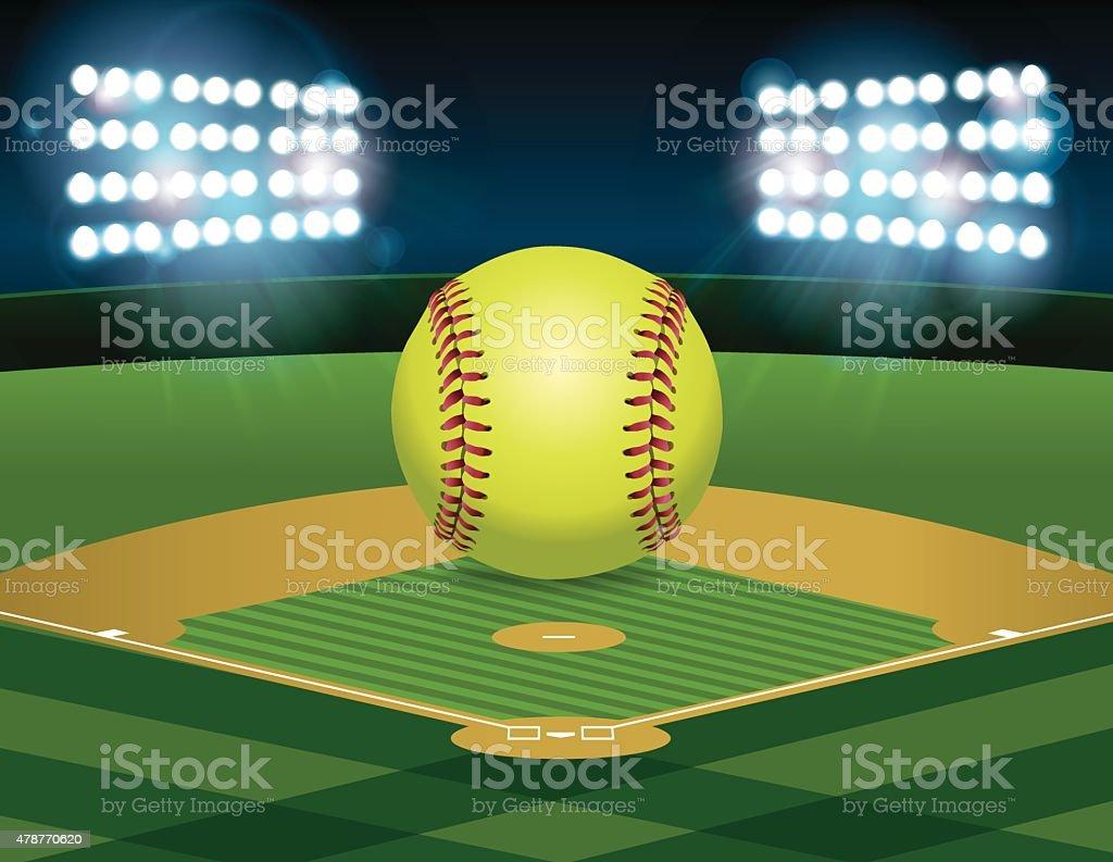 A yellow softball sitting on an illuminated softball field at night....