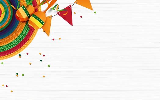Sombrero, maracas, confetti on white wooden background.