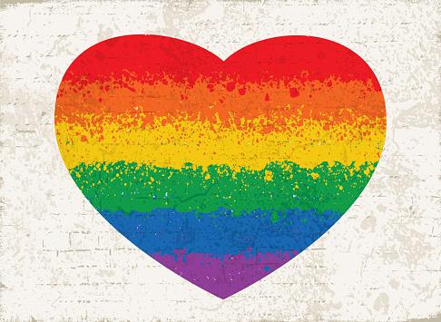 Splatter paint rainbow flag heart shape over a wall texture