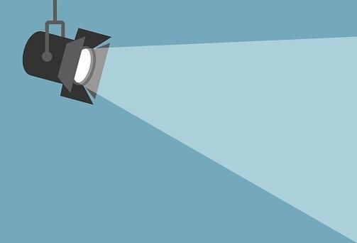 Spotlight shining flat illustration. Movie spotlight on blue background. Vector flat illustration