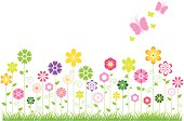 Spring field full of flowers and flying butterflies.