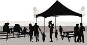 Illustration of cartoon silhouette people at an outdoor festival.  Some kids are there and a tent with a picnic table, balloons, and people sitting in bleechers.