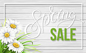 Spring sale frame with chamomiles and grass on wooden background. Spring sale text. Background for invitation, discount offer or flyer. Realistic detailed vector template.