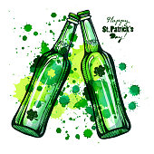 Two beer bottles, engraving for St. Patrick's Day on the background of splashes.