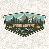 Stay wild, outdoor adventure patch. Vector. Concept for shirt or print, stamp or tee. Vintage typography design with mountains and forest silhouette. Outdoor adventure badge.