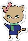 sticker of a cute cartoon cat in winter clothes