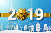 Stock Vector 2019 Happy New Year background with golden gift bow, ribbon and Origami Decoration background with Houses and trees on the hills.