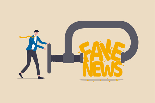 Stop fake news and misinformation spreading on internet and media concept, businessman leader squeezing and destroy the word fake news.