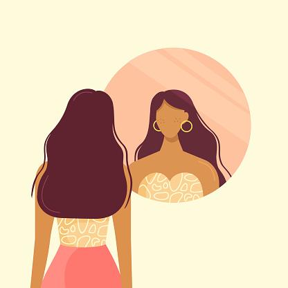 Stylish beautiful girl looks in the round mirror.