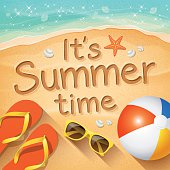 """Summer Background with beach summer accessories and text written in the sand """"It's Summer time"""""""
