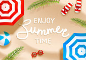 Summer  beach background with sun umbrellas, flip flops, sunglasses, ball and palm leaves on sand