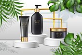 istock summer cosmetics background, advertisement with palms ans black cream bottles with golden lids and sunshine spots and golden frame on white stand. 1334787632