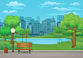 Summer day in the park. Wooden bench, trash can and street lamp on an asphalt park trail with lush green trees and bushes. Green meadow, lake or river, city and blue sky with clouds in the background.