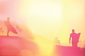 Surfers Silhouettes at the beach against the sun. Pink Surfers on a background with sunlight effects. The Size of illustration is 200x300 mm or 2 to 3 proportionally. Eps 10. Horizontal orientation. This file contains transparency effects, gradient fills.