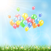 Sunny background with grass and balloons