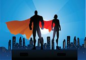 A vector illustration of a couple of superhero in silhouette with city skyline in the background. AICS5 file included. Space for copy available.