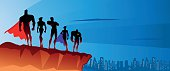 A silhouette style vector illustration of a superhero team on top hill with city skyline in the background. Perfect for Facebook cover or website header. AI CS5 file included.