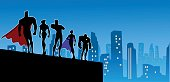 A silhouette style illustration of a superhero team with a city skyline in the background. Wide space available for your copy. AICS5 file included.