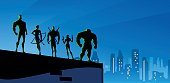 A silhouette style illustration of a team superhero in an American big city at night. Perfect for your website header. AICS5 file included.