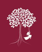 Elegant silhouettes of a tree and a girl in a swing.