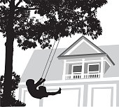 A vector silhouette illustration of a young boy swinging on a tree swing infront of his home.