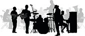 A vector silhouette illustration of a rock band performing with a symphony in the background.