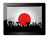 Tablet with soccer filed and fans cheering over Japan flag.