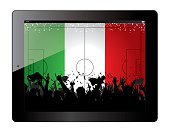 Tablet with soccer filed and fans cheering over Mexico flag.