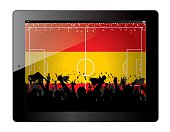 Tablet with soccer filed and fans cheering over Spain flag.