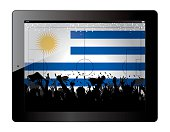 Tablet with soccer filed and fans cheering over Uruguay flag.
