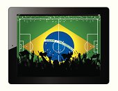 Tablet with soccer filed and fans cheering over Brasil flag.