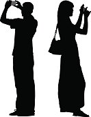 Vector silhouette of a man and a woman taking photographs with their smart phones.