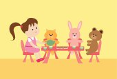 A little girl having a tea party with her stuffed animals
