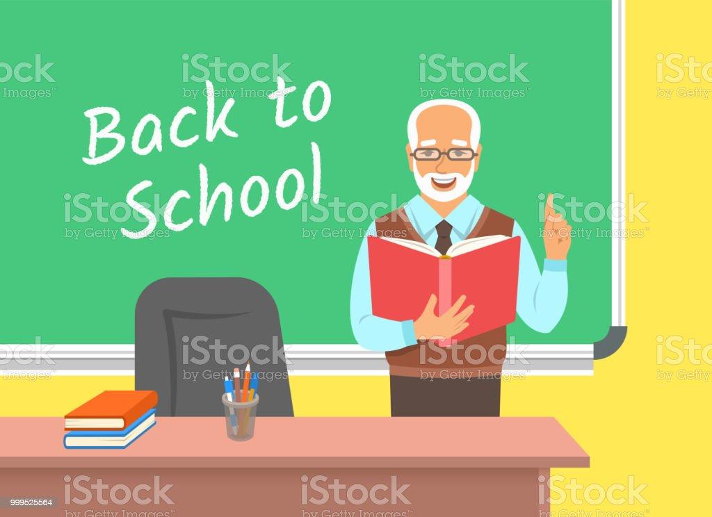 Teacher reads book near blackboard in classroom