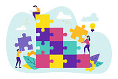 Team Metaphor. People Connecting Puzzle Elements. Teamwork, Cooperation, Partnership. Man Sitting with Laptop on Top, Male and Female Characters Set Up Construction. Cartoon Flat Vector Illustration
