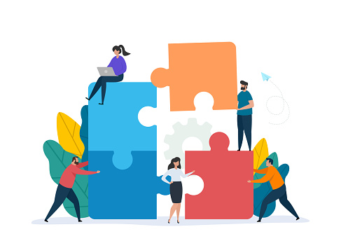 Teamwork concept with building puzzle. People working together with giant puzzle elements.