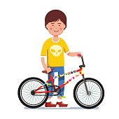 Teen kid standing next to sticker bombed bmx bike