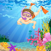Teenage boy snorleling underwater on summer time, there are some colorful sea anemone on the ocean floor.