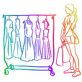 Young woman shopper standing next to a clothes rack full of dresses and looking in envy.
