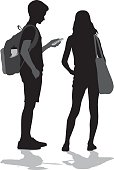 A vector silhouette illustration of two preteens standing together with the young boy looking at his cell phone.  A young girl stands beside him.
