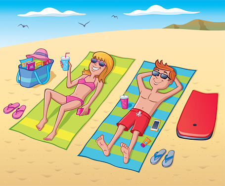 Teens Laying Out At The Beach Getting Sun And Relaxing