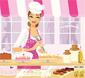 A pretty young woman in her bakery, icing a cake. Pastries, cakes and goodies laid out at the counter. Delicious!