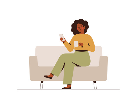 The black businesswoman is sitting on the couch with a mobile phone at the break time.