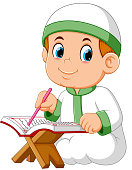 the boy is sitting and reading al quran