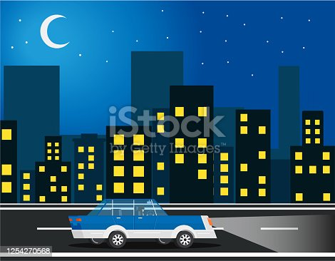 The car rides through the middle of the city. Night blue city with light from windows and moon with stars.