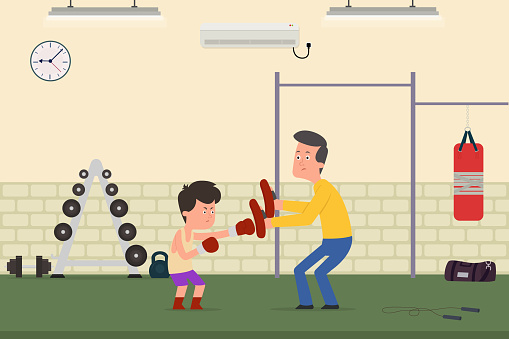 the child is being trained to box with the trainer in the gym